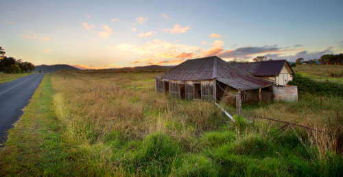 An abandoned house sits alone by the side of a rural highway, whilst the sunrises from the mountains in the distance.