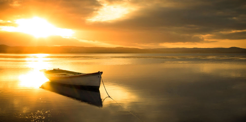 A peaceful and serene looking boat sits docked on the lake in the glowing afternoon sunlight.