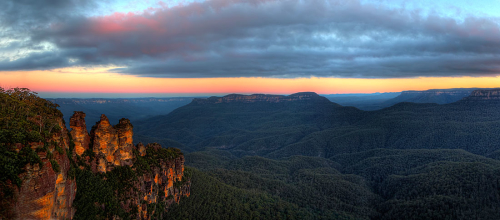 The Late afternoon sun sets in the west casting the final light onto the rock faces of the Three Sisters, Katoomba, NSW, Australia