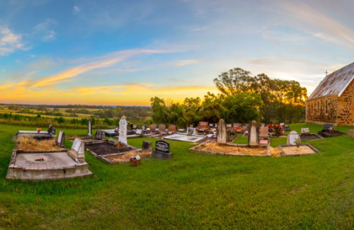 A cute little church and graveyard overlooking a valley at sunset.
