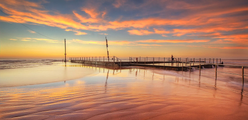 Glorious reflections on the sand in Mona Vale as the sun rises over the Tidal Pool