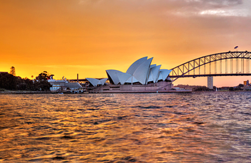 The orange afterglow of sunset lingers over the Opera House and Sydney Harbour Bridge, as a lone yacht bobs nearby.