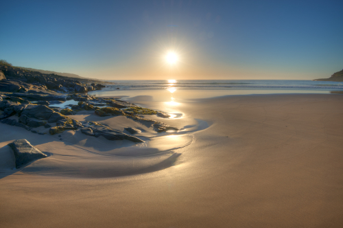 Smooth sand and stunning shadows fall over Merry Beach in the early morning light