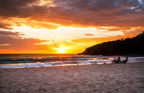 A couple sit on the shores of Merry Beach in Deck chairs and see in the new day