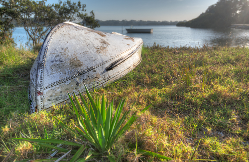 an overturned boat rests ashore at Moruya Heads, NSW, Australia