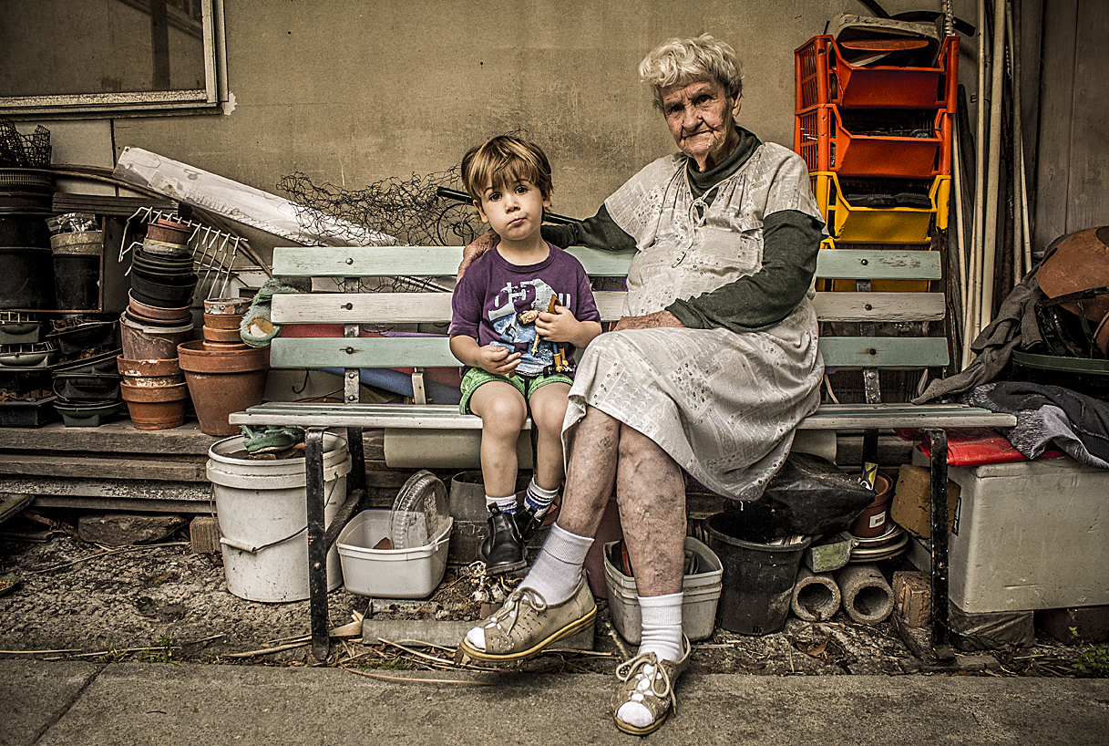 An elderly woman and her great grandson in her garden which is over laden with a lifetimes worth of possessions and clutter.